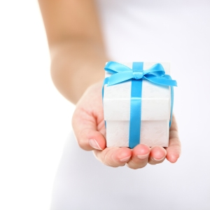 Gift box / present or christmas gift hand close up. Decorative gift box tied with a turquoise ribbon and bow carefully cupped in female hands as she gives a surprise present to a loved one. Isolated.